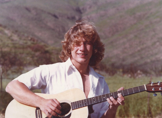 Young Vern with guitar in field